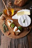 Camembert cheese on paper, grapes, nuts and honey in glass bowl on on cutting board on wooden backgr