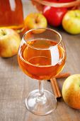 Apple cider in wine glass and bottle, with cinnamon sticks and fresh apples on wooden background