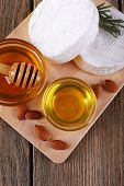 Camembert cheese, honey in glass bowl on cutting board on wooden background