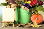 Beautiful autumn composition with paper blank on bright background
