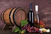 Wine in bottles, Camembert and brie cheese, grapes and wooden barrel on wooden table on wooden backg
