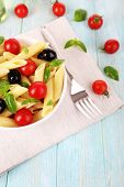 Pasta with tomatoes, olives and basil leaves in bowl on napkin on wooden background