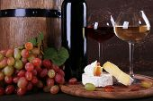 Supper consisting of Camembert cheese, wine and grapes on cutting board and wine barrel on wooden ta