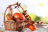 Pumpkins in wicker basket and leaves on wooden table on natural background