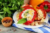 Composition with prepared stuffed peppers on plate and fresh herbs, spices and vegetables, on wooden background