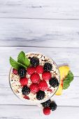 Healthy breakfast - yogurt with  fresh fruit, berries and muesli served in glass bowl on color woode