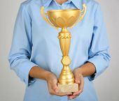 Woman holding trophy cup on color background
