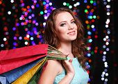 Beautiful young woman with shopping bags on bright lights background