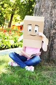 Woman with cardboard box on her head with sad face reading the book, outdoors