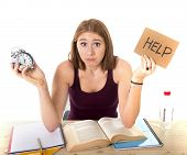stock photo of time study  - young beautiful college student girl studying for university exam in stress asking for help holding alarm clock test deadline time pressure sitting on desk in education concept - JPG