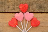 Red Heart shaped lollipops on wood backdrop