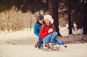 Happy Couple Riding A Sled