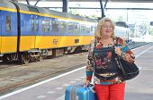 Woman with big suitcase at a train station in Rotterdam