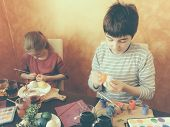 Brother And Sister Painting Easter Eggs At Home