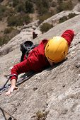 picture of climbing wall  - Young white man climbing a steep wall in mountain, rock-climbing extreme sport, summer season. Horizontal orientation
