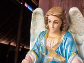 An angel with white wings at the front of wooden church