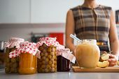 Closeup On Jar With Homemade Apple Jam And Young Housewife In Ba