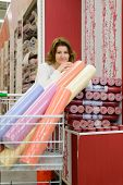 Woman buys wallpaper in  store