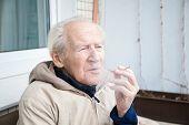 Old Man Exhaling Smoke