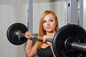 Girl doing exercises with barbell in gym