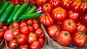 Red tomatoes and cucumbers in baskets