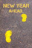Yellow Footsteps On Sidewalk Towards New Year Ahead Message