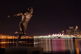 stock photo of inlet  - The statue of Harry Jerome crossing the finish line beside the Stanley Park seawall at night - JPG