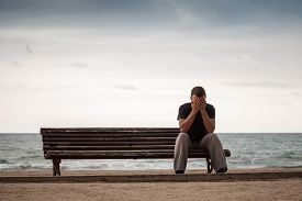 stock photo of sitting a bench  - Sad man sits on the old wooden bench on the sea coast - JPG