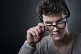 stock photo of flirty  - Cool young man adjusting his stylish glasses with flirty expression - JPG