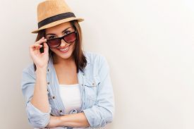picture of candid  - Portrait of beautiful young woman in glasses and funky hat adjusting her glasses and smiling while standing against brown background - JPG