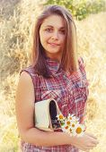 picture of haystack  - portrait of a pretty girl with a magazine and a bouquet of daisies on a background of haystacks - JPG