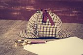 pic of private investigator  - Deerstalker Hat and magnifying glass on Old Wooden table - JPG
