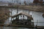 picture of pergola  - Old pergola covered with reeds on the bridge over frozen river - JPG
