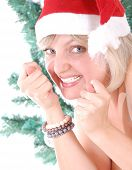 stock photo of saxy  - beautiful playful Santa girl with figas against the Christmas tree - JPG
