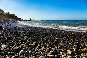 stock photo of atlantic ocean  - Wild stone beach on coast of the Atlantic ocean with waves and sky with clouds and skyline or horizon in Tenerife Canary island Spain at spring or summer - JPG
