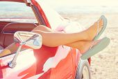 picture of car-window  - Relaxed woman legs and flip flops in a car window on the beach - JPG