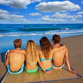 foto of couple sitting beach  - friends group couples sitting in beach sand rear view back looking to the sea - JPG
