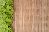 picture of bamboo leaves  - lettuce leaves laid on both sides on a bamboo table cloth - JPG