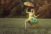 stock photo of wearing dress  - Girl levitates over the green field on the umbrella - JPG