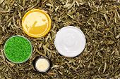 foto of scrubs  - Variety of cosmetic body care products in dry sea buckthorn leaves - JPG