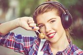 stock photo of lollipop  - Portrait of pretty attractive girl hipster headphones and a lollipop - JPG