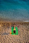 picture of top-hat  - Woman in swimsuit and hat lying on the green towel on the beach - JPG