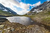 picture of italian alps  - Flowing waters from melting snow feeding high altitude alpine lake in idyllic uncontaminated environment once covered by glaciers in the italian french Alps - JPG