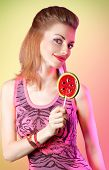 foto of lollipop  - Portrait of mischievous redhead girl smiling with big lollipop in the form of watermelon - JPG