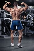 stock photo of hamstring  - Strong Athletic Man Fitness Model Torso showing muscles in gym - JPG