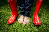 picture of lady boots  - Closeup photo of female feet standing on green grass next to red rain boots - JPG