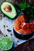 picture of over counter  - Salmon steak avocado lime and parsley over old wooden texture  - JPG