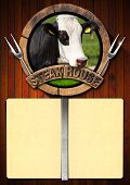 image of cow head  - Wooden background with yellow empty paper wooden symbol with head of cow two forks and text Steak house - JPG