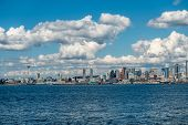 image of puffy  - White puffy clouds hover over the Seattle skyline on a sunny day - JPG