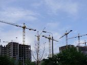 stock photo of construction crane  - construction cranes on construction of buildings against the sky - JPG